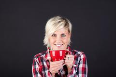 Young smiling woman enjoying coffee Stock Photos