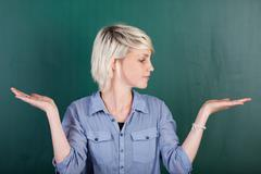 woman with empty palms against chalkboard - stock photo