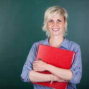 Woman with folder in front of chalkboard Stock Photos