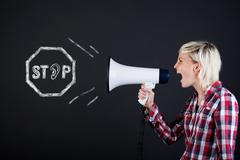 side view of woman yelling into megaphone - stock photo
