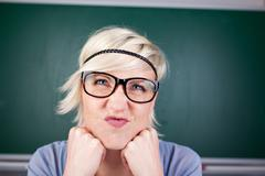 blond woman contorting her face against chalkboard - stock photo