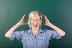 Blonde woman shouting by chalkboard Stock Photos