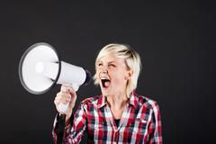 blonde woman shouting into megaphone - stock photo
