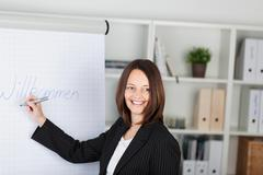 Businesswoman writing welcome sign in office Stock Photos