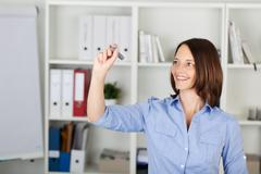 Happy businesswoman writing on invisible screen Stock Photos