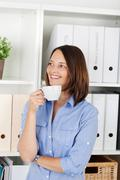 Woman enjoying a cup of coffee at the office Stock Photos