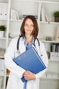 Female doctor carrying a large file Stock Photos