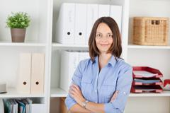 Confident businesswoman with arms crossed in office Stock Photos