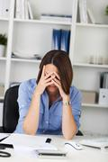 sad businesswoman sitting at desk - stock photo