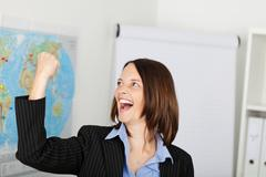 businesswoman with clenched fist celebrating victory - stock photo
