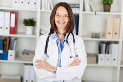 Female doctor with arms crossed standing against shelves Stock Photos
