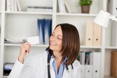 Doctor holding blank visiting card against shelves Stock Photos