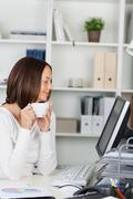 Businesswoman holding coffee cup while looking at computer Stock Photos