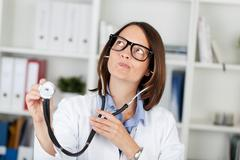 Doctor holding stethoscope while making faces Stock Photos