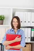 Businesswoman holding binder in office Stock Photos