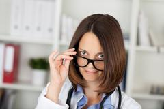 Female doctor looking over eyeglasses in clinic Stock Photos