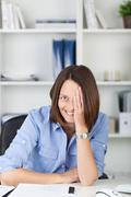 playful businesswoman covering eye with hand in office - stock photo