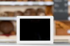 Digital tablet on bakery shop counter Stock Photos