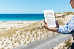 woman reading e-reader at fence on beach - stock photo