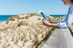 Woman by the beach reading on tablet-pc Stock Photos