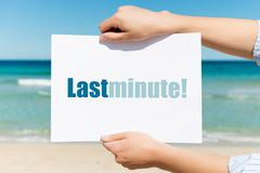 woman's hands holding placard with last minute sign on beach - stock photo