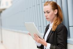 Serious businesswoman reading tablet pc Stock Photos