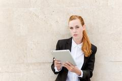 Confident businesswoman reading tablet pc Stock Photos