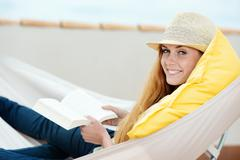smiling woman reading book in hammock - stock photo