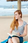 Smiling redhead woman with book on beach Stock Photos