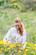 smiling redhead woman sitting amid flowers in field - stock photo