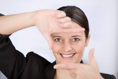 businesswoman looking through hand frame - stock photo