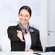receptionist offering handshake at counter - stock photo