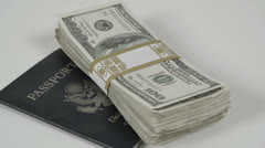 Passport rotating with stack of money Stock Footage