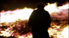 Old woman walks away from fire in silhouette - stock footage