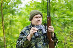 Hunter with optical rifle and binoculars in the woods Stock Photos