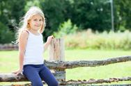 Stock Photo of shy caucasian child sitting on fence on sunny day. copyspace
