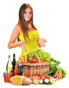 Stock Photo of young woman with assorted grocery products isolated on white background
