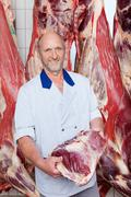 Happy butcher holding a freshly cut piece of beef Stock Photos