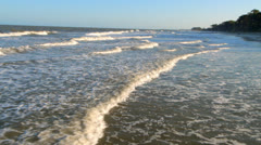 Flying over waves on the beach with a helicopter low altitude Stock Footage