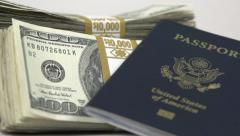 Passport leaning up against stack of money Stock Footage