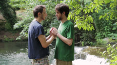 Two young boys kiss each other near a river: gay, love, kissing, homosexual Stock Footage