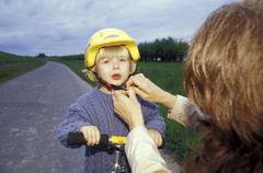 Mother adjusting son's (3-5) cycling helmet Stock Photos