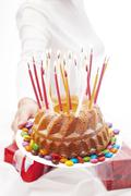 Woman holding out birthday cake with candles Stock Photos