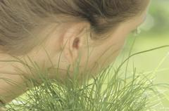 Girl listening to grass growing - stock photo