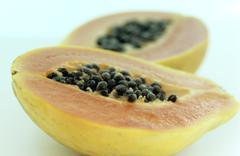 Two halves of pawpaw fruit - stock photo