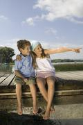 Stock Photo of Boy and girl (6-9) sitting on jetty