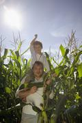 Father with boy on his shoulders coming out of a maize field - stock photo