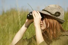 Young woman using binoculars in field - stock photo