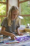 Girl using stencil for drawing - stock photo