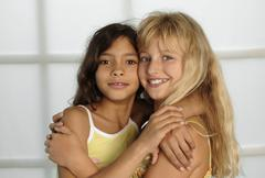 Two girls (8-11) cheek to cheek with arms around, portrait Stock Photos